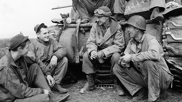 Ernie Pyle (with goggles) converses with a tank crew from the 191st Tank Battalion, US Army at the Anzio Beachhead in 1944