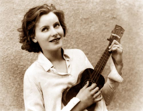 A very young Garbo strumming a ukulele