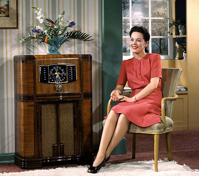 An attractive woman sits listening to a vintage radio