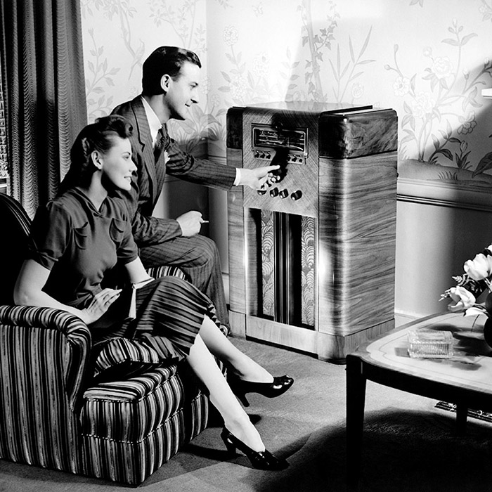 A vintage photo of a couple listening to the radio